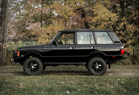 A vintage black Range Rover with treaded tires in front of a bush on the grass
