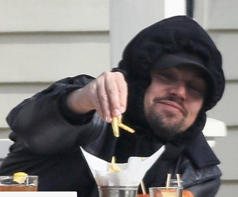 Leonardo Dicaprio enjoying French Fries with a smile on his face