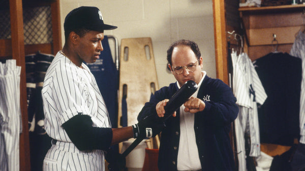 George Costanza and New York Yankee holding a black bat in the locker room