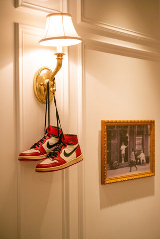 A pair of Red and Black Nike Air Jordan 1 sneakers hanging on a hotel room light