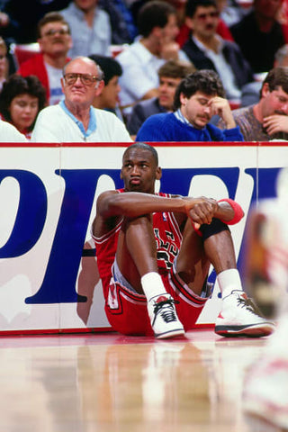 Michael Jordan sitting on the sideline at a Chicago Bulls game waiting to check in