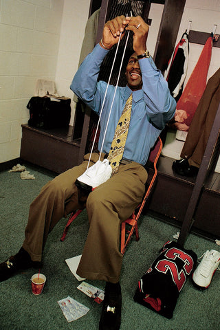 Michael Jordan sitting in the locker room in a suit lacing up his sneakers with a big smile on his face