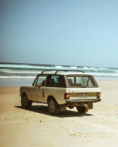 A cream Range Rover parked on the sand on a beach in front of a beautiful ocean