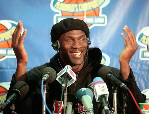 MIchael Jordan in a Chicago Bulls practice jersey and headphones in front of press conference microphones