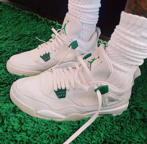 Green and White Nike Air Jordan 4's standing on green grass