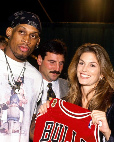 Cindy Crawford holding up a Red Chicago Bulls jersey in front of NBA star Dennis Rodman