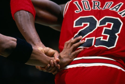 Michael Jordan in a Red and Black Chicago Bulls jersey holding a players arm