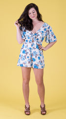 blue and white floral romper with flutter sleeves and pockets. Perfect summer romper!