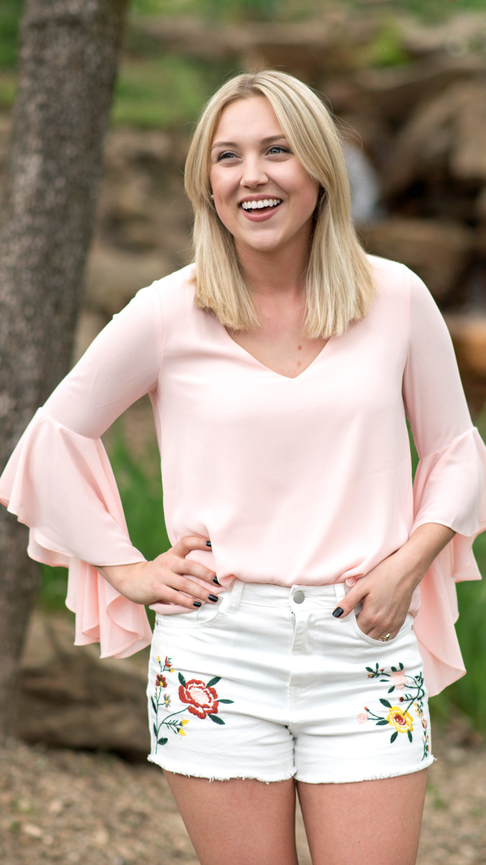 white embroidered shorts with a frayed hem worn with pink top with flowy sleeves and a dropped neck in the back
