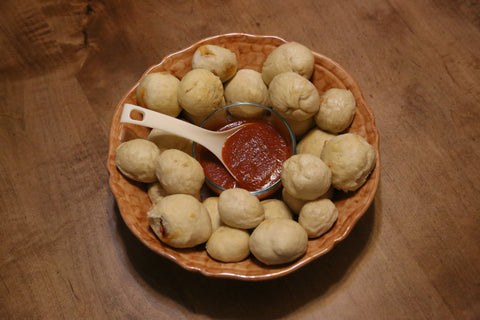 Cooked dough balls positioned around pizza sauce.