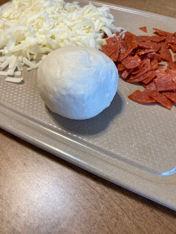 A ball of dough with cheese and pepperoni on a Norwex cutting board.
