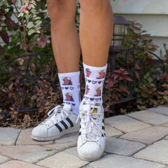 This is an image of white crew socks with multiple faces and hearts.