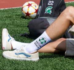 "This is an image of white crew socks with ""Soccer Goals"" and a customized number."