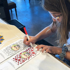 This is an image of a girl coloring in the Custom Coloring Book Socks.