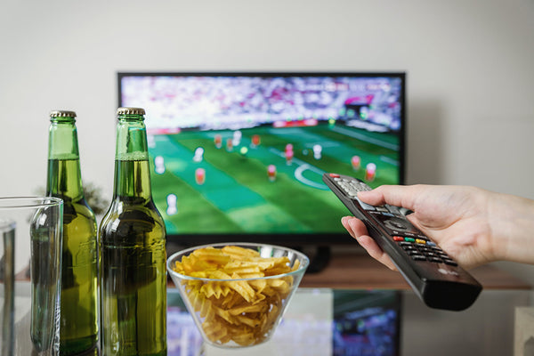 This is an image of a person watching a football game on television, drinking beer, and eating snacks.