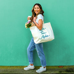 This is an image of a girl holding the Sorority Name in Watercolor Stylized Script Tote Bag.