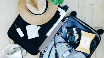 Open suitcase with clothes, straw sun hat and camera