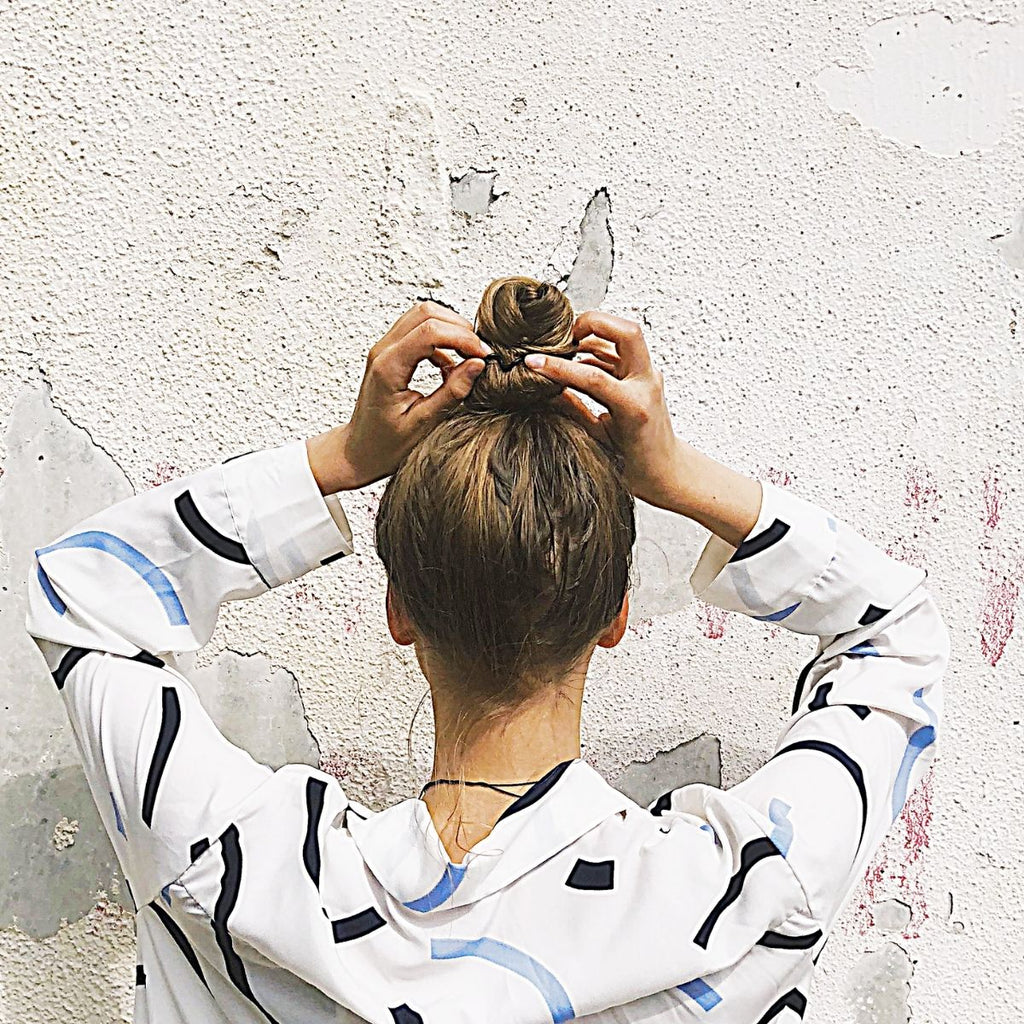 Woman in white and black abstract jumper facing a wall and styling her hair