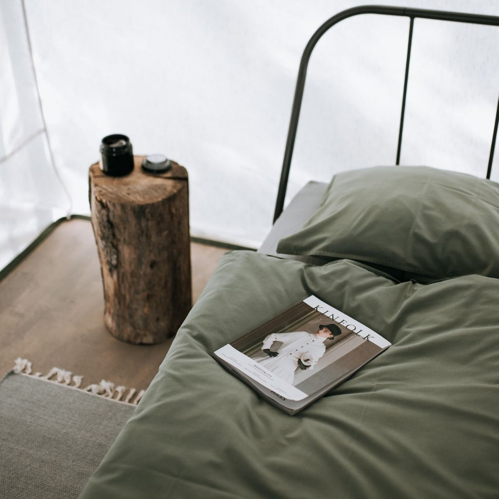Inside of tent with metal bed and dark green covers for best camping essential tips