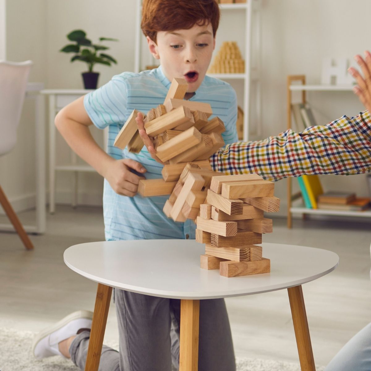 Young boy playing game of Jenga on a staycation