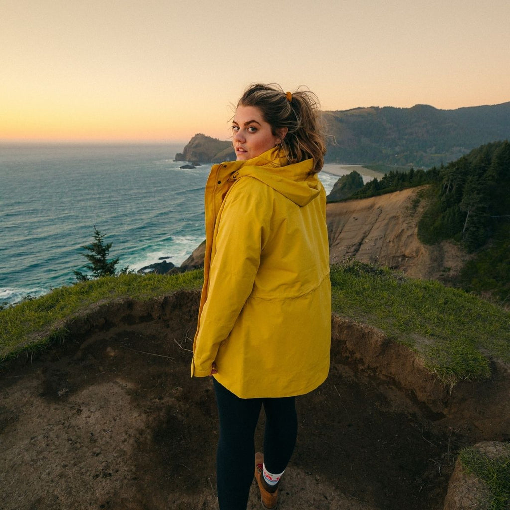 Woman in yellow raincoat standing on top of a cliff for staycation essentials