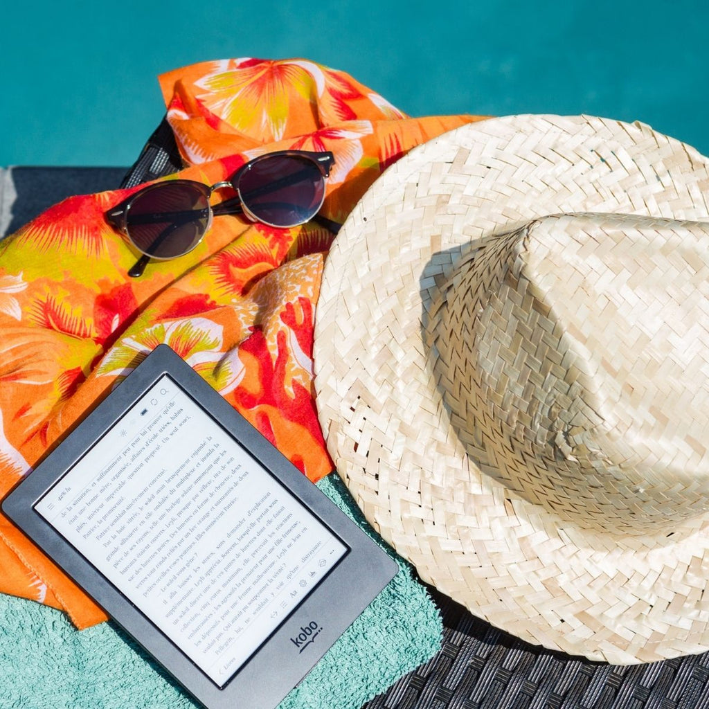 Kindle book, straw sun hat, sunglasses and orange cover up for staycation essentials
