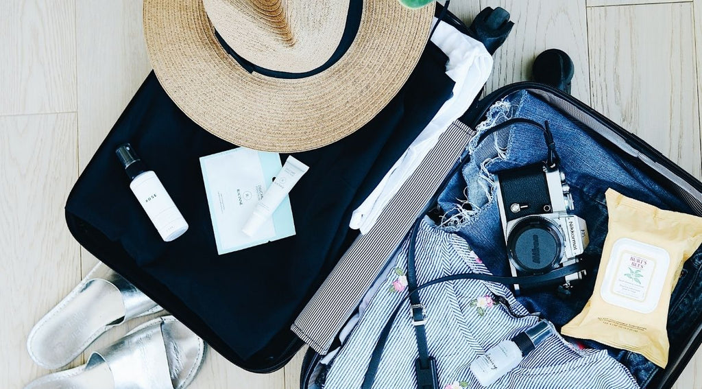 Open suitcase for staycation essentials with clothes, straw hat and camera