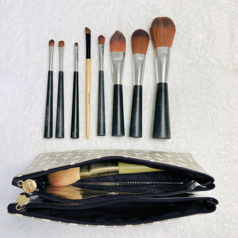 Makeup brushes in folding makeup bag with compartments