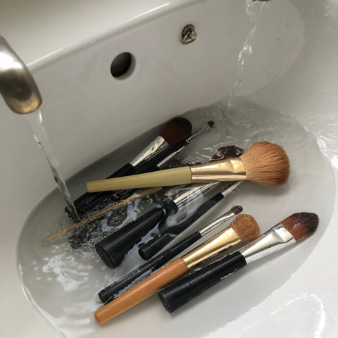 makeup brushes being washed ready to go back into a clean makeup bag
