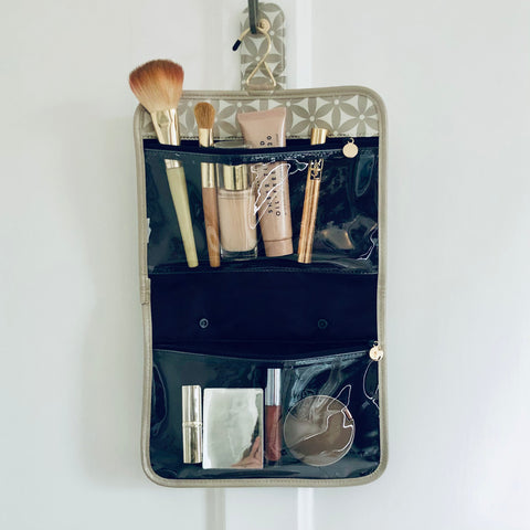 Hanging toiletry bag with makeup and cosmetics in clear compartments
