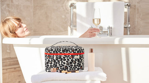 Woman relaxing in bath with leopard print beauty bag vanity case in foreground