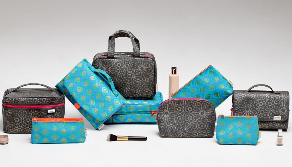 collection of wash bags and make up bags in blue and charcoal