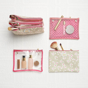 Flat lay of 3 piece cosmetic bag with clear and floral pattern sections