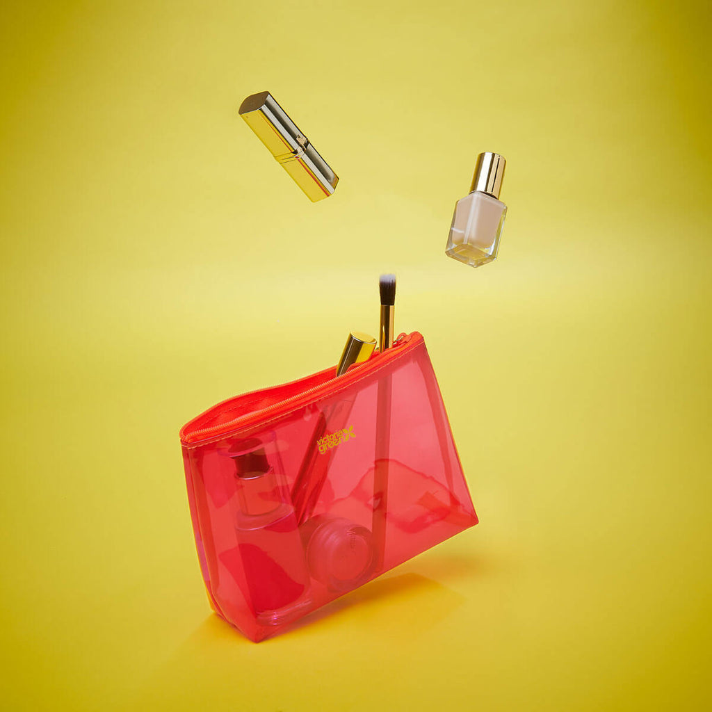 clear pink small makeup bag with products