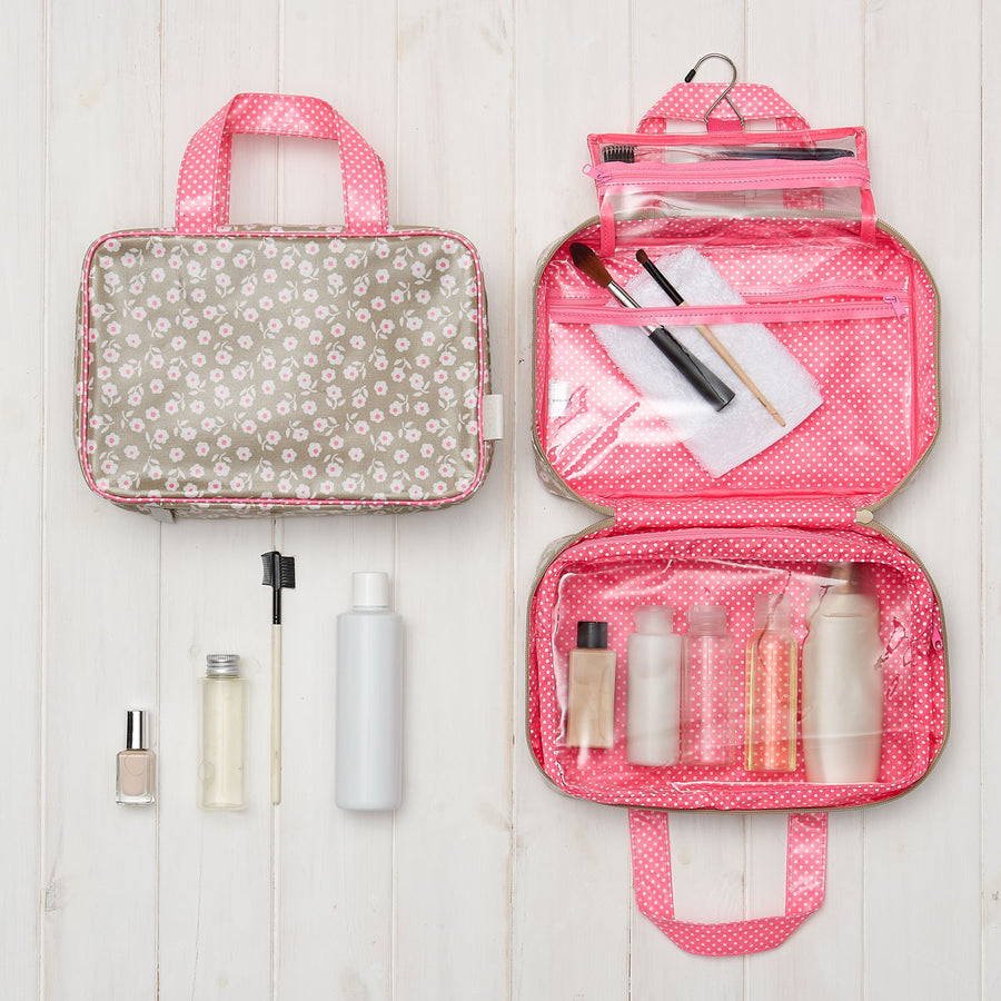 hanging toiletry bag in daisy sage with pink handles and transparent compartments