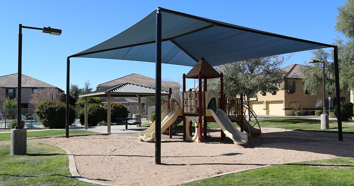 Hip shade structure over playground equipment