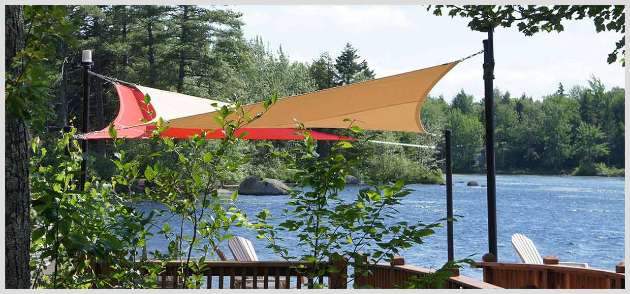 Two shade sails on a patio by a lake in Northfield, MA