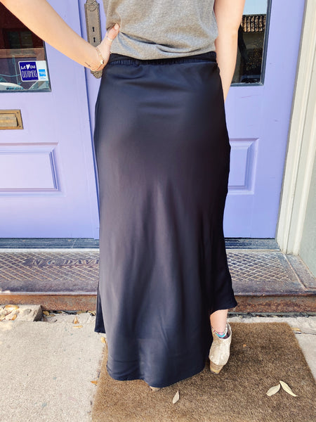 Satin Midi Skirts at Multitudes Boutique - The Black Satin Midi Skirt is adorable and practical! This Black Satin Midi Skirt can be dressed up or down, has a faux wrap with tie at the waist, is lined and has elastic in the back. You will LOVE this faux Wrap Midi Skirt! Multitudes Boutique. Cutest Online Clothing Store.