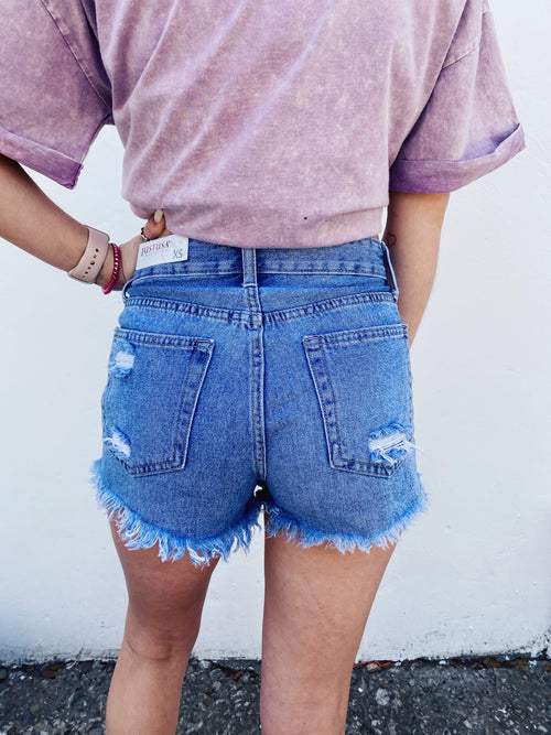 High Rise Denim Shorts at Multitudes Boutique - The Bailey Button Down Denim Shorts in Light Wash are a MUST! These Distressed Jean Shorts have an exposed button fly, are comfy and soft, and get better with wear. These Distressed Denim Shorts are perfect! Multitudes Boutique. Cutest Online Clothing Store.