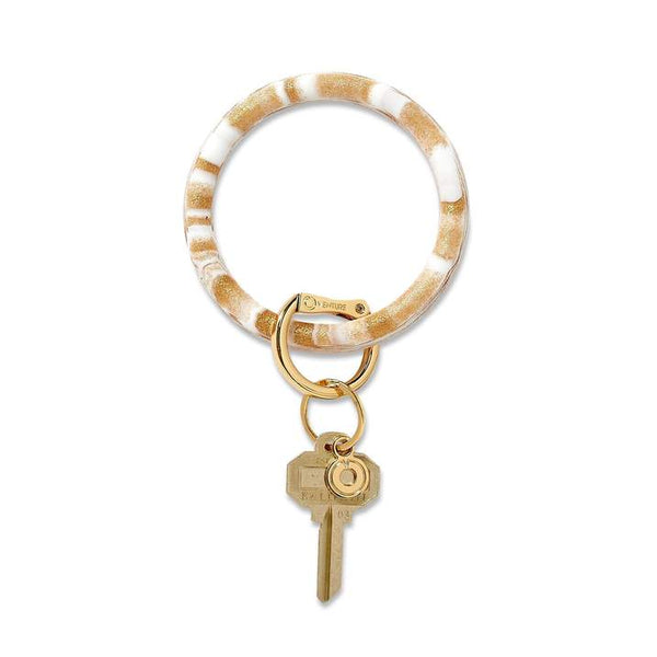 Silicone Big O® Key Ring MARBLE The Gold Rush Marble Silicone Key Ring is Crafted from a white silicone base, this ultra-durable waterproof collection is marked by a swirling marbled pattern. The Original Big O Key Ring is a one-size-fits-all bracelet key ring. Oventure. Multitudes Boutique. Cutest Online Boutique.