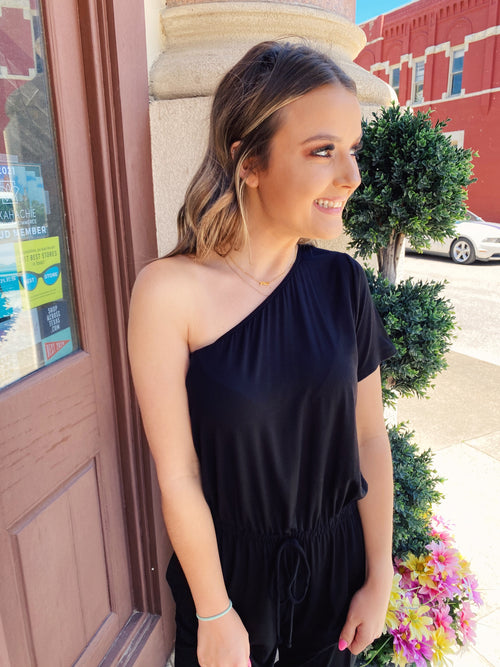 The Jennia One Shoulder Jumpsuit in Black is perfect for the girl on the go! It is styled as a Jogger Jumpsuit with an elastic waistband with a tie. Pack this Black Casual Jumpsuit in your bag or wear it on the plane! Runs True to Size. One Shoulder Jumpsuit. Multitudes Boutique. Cutest Online Clothing Store.