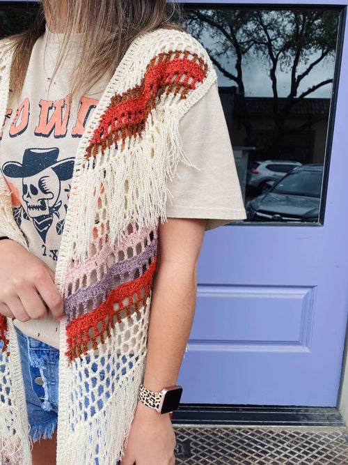 Every closet needs The Miranda Fringed Sweater Vest! This Fringed Hem Crochet Kimono is sleeveless, has diagonal stripes in sunset hues, a loose weave, and fringe details. Wear this boho inspired Women's Sleeveless Cardigan over shorts and a crop top. Multitudes Boutique. Cutest Online Clothing Store.