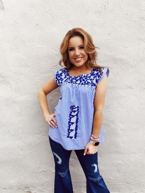 The Adeline Embroidered Top by J. Marie Collections is a fun twist on the traditional Mexican Embroidered Top. This Mexican Top has dark blue and white embroidery on a blue and white striped background. Pair with your dark or white denim for a classic summer look. Multitudes Boutique. Cutest Online Clothing Store.