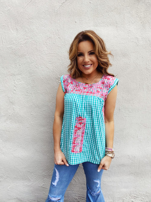 Stay Cool and Look Adorable in The Jill Embroidered Top! This Classic Mexican Top has pink and coral embroidery on a green gingham background. You'll look summer chic when you pair this Embroidered Mexican Top with white jeans or shorts. Runs TTS. Multitudes Boutique. Cutest Online Clothing Store.