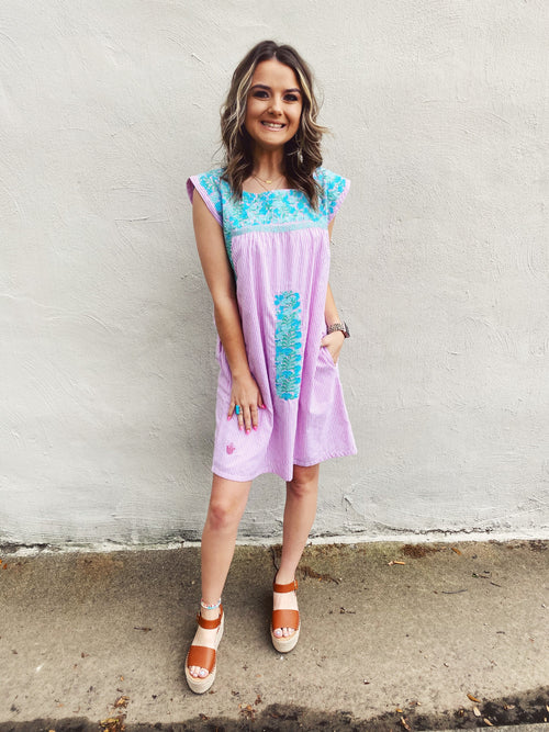 Stay cool and look timeless in The Kaylee Embroidered Mexican Dress by J. Marie Collections! The traditional embroidery is blue and mint on a pink striped Mexican Dress that is fully lined! Embroidered Dresses. Model Wearing a Small. Runs TTS. Multitudes Boutique. Cutest Online Clothing Store.