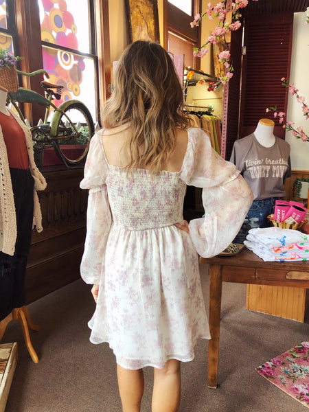 Make the Singing Spring Dress your next MUST-HAVE dress this season! It's perfect for Easter, for all those summer weddings and showers, and even your next date night! We love the simple lilac floral print all over, the smocked bodice, and the sheer bubble sleeves. Best Online Boutique. Multitudes Boutique. Free Shipping.
