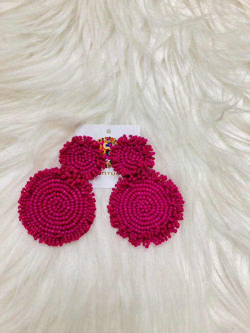 "We LOVE the Purple Cynthia Earrings! Honestly, these are really more magenta than purple, so please take note. These dangling seed bead earrings are approximately 2"" long and are made of the prettiest magenta color. The beads are decorated in two circles with fringe, backed by felt. They will make all your summer outfits POP!  The color is more magenta than purple 2"" - 2.5"" long"