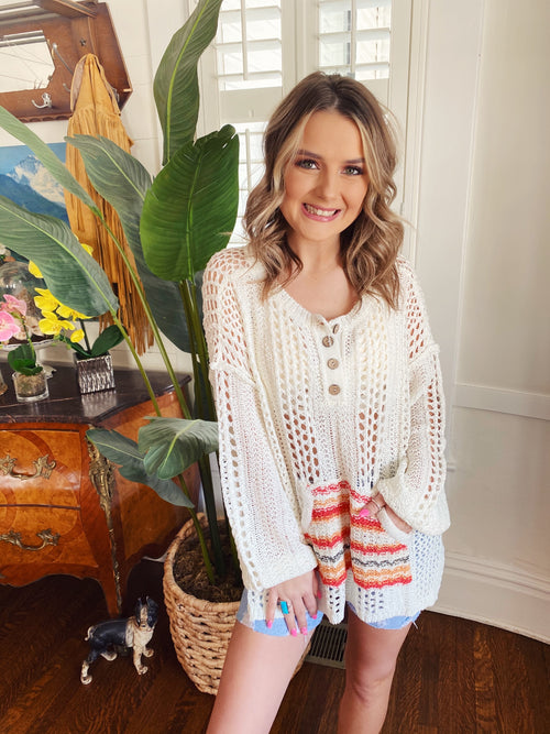 Beach Sweaters at Multitudes Boutique - The Sunset Stripe Loose Beach Sweater is the perfect Summer Sweater! This Loose Knit Sweater is oversized, has a kangaroo pocket woven in summer hues, and four buttons at the neck. This Summer Sweater is perfect for beach walks! Multitudes Boutique. Cutest Online Clothing Store.