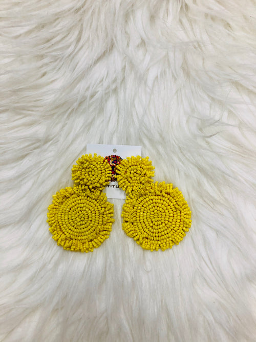 "We LOVE the Yellow Cynthia Earrings! These dangling seed bead earrings are approximately 2"" long and are made of the brightest yellow color. The beads are decorated in two circles with fringe, backed by felt. They will make all your summer outfits POP! Approx 2.5"""