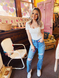 Distressed Mom Jeans at Multitudes Boutique - The Janie Mom Jeans are lightwashed. These Destroyed Mom Jeans are a straight fit and ankle length. These High Rise Mom Jeans are distressed on the thighs and knees, and have a regular hem. Lightwash Mom Jeans. Multitudes Boutique. Cutest Online Clothing Store.